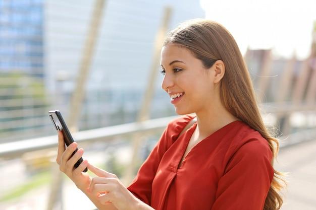 Braziliaanse blanke zakenvrouw met behulp van online app winkelen op slimme telefoon in de straat