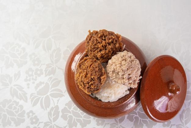 Braziliaanse cocada (kokosnotensuikergoed) geplaatst in een keramische pot op een tafel met wit tafelkleed, bovenaanzicht.