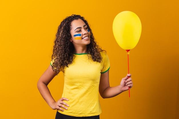 Braziliaanse fan met een gele ballon met vrije ruimte voor tekst. spelpromotie in brazilië