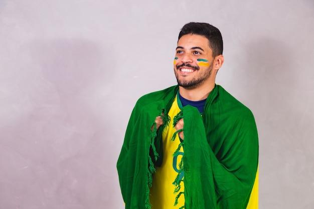 Braziliaanse fan met een vlag op zijn rug die juicht voor de overwinning van brazilië