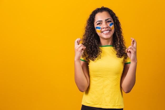 Braziliaanse fan met gekruiste vingers die geluk op gele achtergrond vibreren