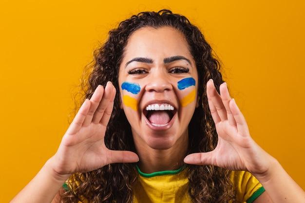 Braziliaanse fan met haar gezicht geschilderd in blauw en geel voor de braziliaanse wedstrijd. braziliaan die de onafhankelijkheid van brazilië viert. 7 sept. braziliaanse fan schreeuwt van geluk