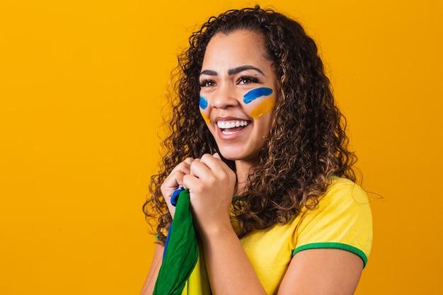Braziliaanse fan met haar gezicht geschilderd in blauw en geel voor de braziliaanse wedstrijd. braziliaan die de onafhankelijkheid van brazilië viert. 7 september