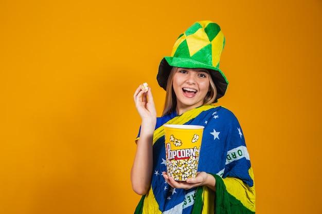 Braziliaanse fan met popcorn om de wedstrijd te bekijken. entertainment- en sportconcept