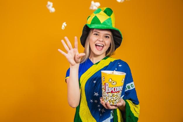 Braziliaanse fan met popcorn om de wedstrijd te bekijken. entertainment, sport en patriottisme concept