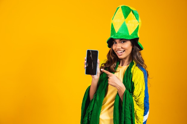 Braziliaanse fan. portret, braziliaanse fan die haar mobiele telefoon toont, verkleed als voetbalfan of voetbalwedstrijd op gele achtergrond. kleuren van brazilië.world cup