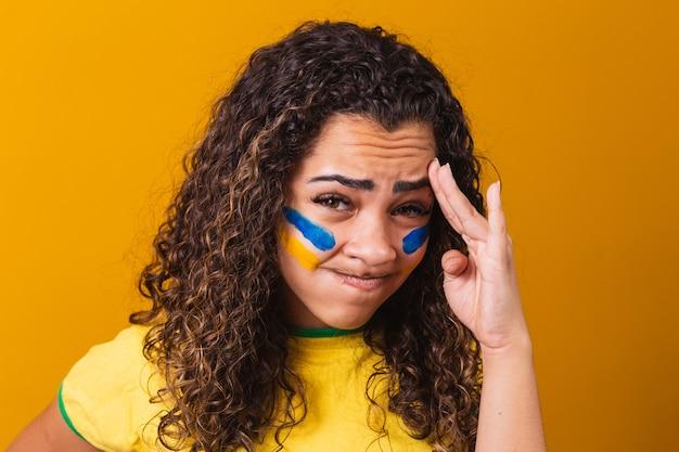 Braziliaanse fan teleurgesteld op gele achtergrond met braziliaanse blouse