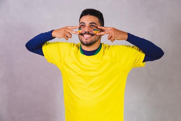 Braziliaanse fan. verf gebruiken als make-up, braziliaanse fan die voetbal of voetbalwedstrijd viert op een grijze achtergrond. kleuren van brazilië.