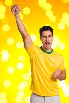 Braziliaanse fan viert feest op gele ruimte