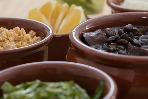 Braziliaanse feijoada, farofa, collard greens en sinaasappel