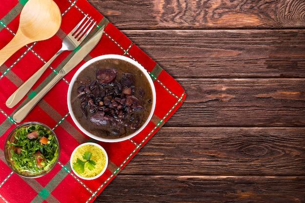 Braziliaanse feijoada. met een houten achtergrond. bovenaanzicht - afbeelding