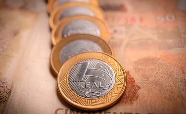 Braziliaanse geldmunten van één real in volgorde die op bankbiljetten staan