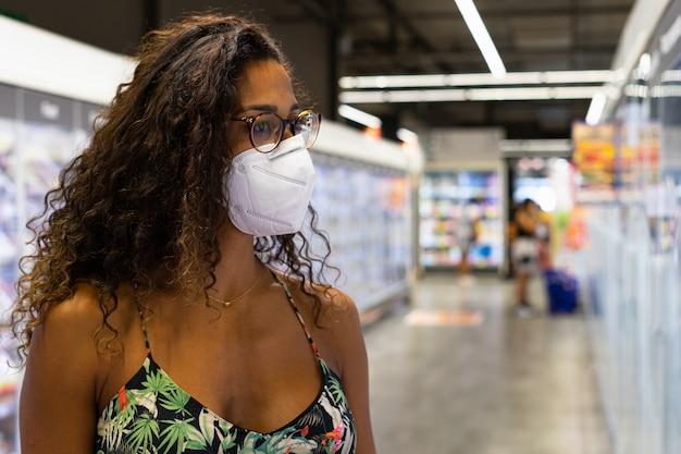 Braziliaanse jonge vrouw die in de supermarkt met masker winkelt. nieuw normaliteitsconcept.