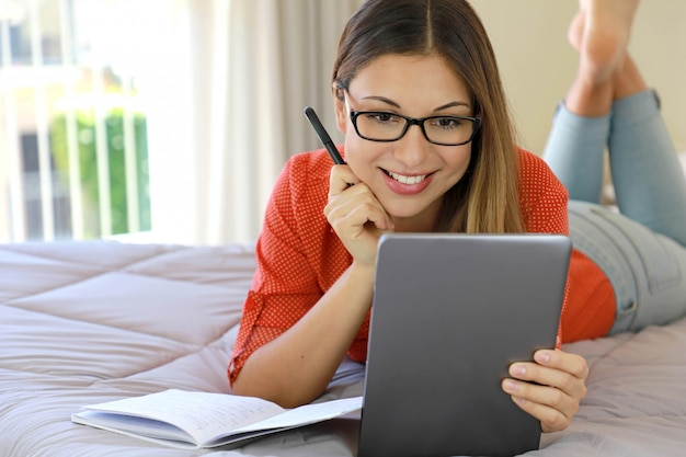 Braziliaanse jonge zakenvrouw draagt een bril video bellen chat afstand webinar online op tablet door webcam of volgt een online cursus.