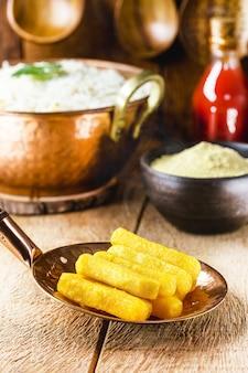 Braziliaanse keuken, polenta genaamd, traditionele braziliaanse frietjes, met maïsmeel en saus aan de oppervlakte, rustieke omgeving,