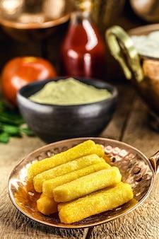 Braziliaanse keuken, polenta genaamd, traditionele braziliaanse frietjes, met maïsmeel en saus