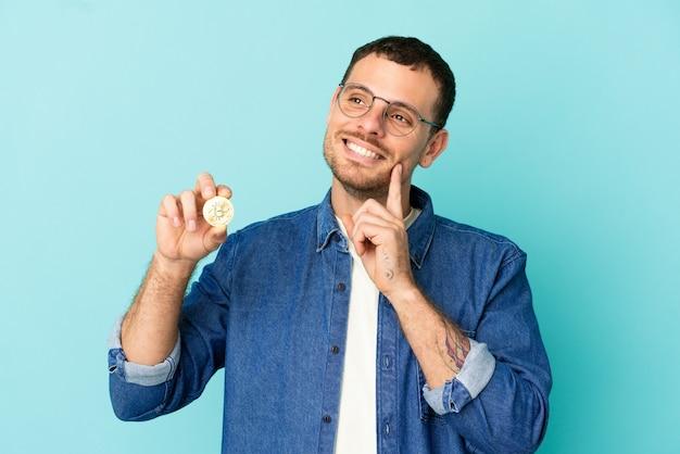 Braziliaanse man die een bitcoin over een geïsoleerde blauwe achtergrond vasthoudt en een idee denkt terwijl hij omhoog kijkt