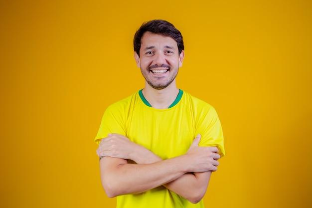 Braziliaanse man met braziliaans t-shirt met gekruiste armen op gele achtergrond