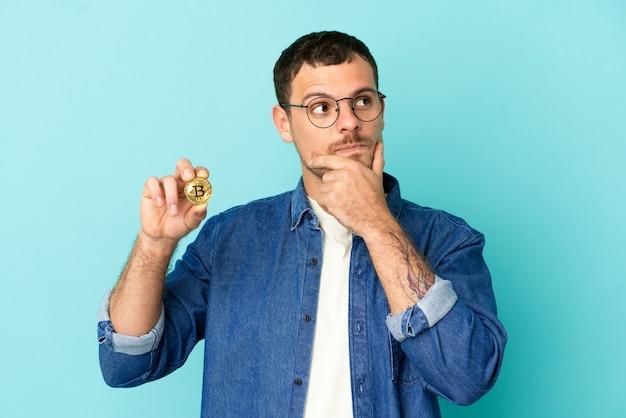Braziliaanse man met een bitcoin over geïsoleerde blauwe achtergrond die twijfels heeft