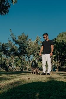 Braziliaanse man met je pitbull-hond in het openbare park. genegenheid en liefdesrelatie tussen mens en dier.