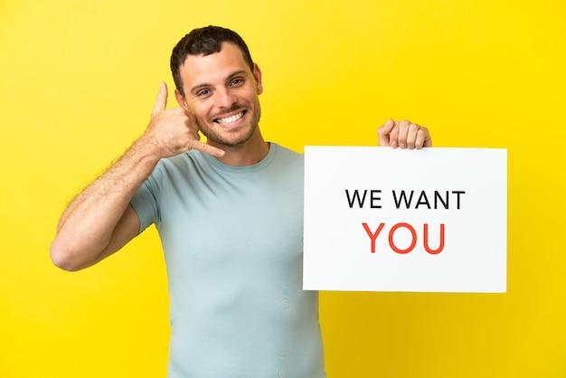 Braziliaanse man over geïsoleerde paarse achtergrond die we want you aan boord houdt en een telefoongebaar maakt