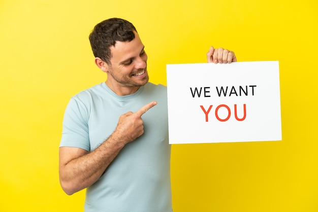 Braziliaanse man over geïsoleerde paarse achtergrond die we want you-bord vasthoudt en erop wijst