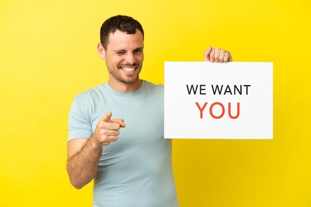 Braziliaanse man over geïsoleerde paarse achtergrond die we want you-bord vasthoudt en naar voren wijst
