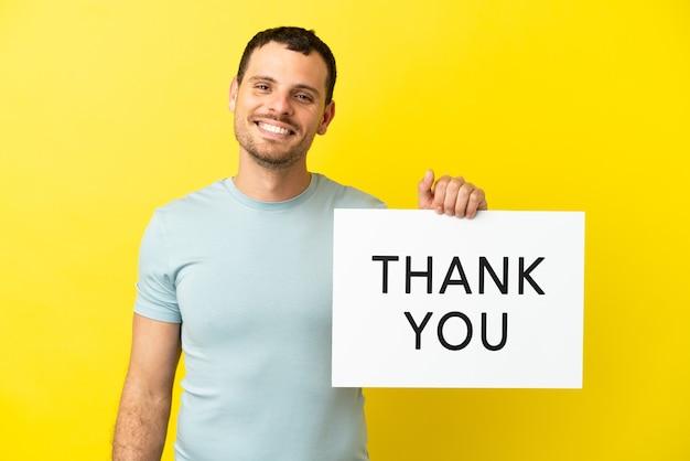 Braziliaanse man over geïsoleerde paarse achtergrond met een bordje met de tekst bedankt met een gelukkige uitdrukking