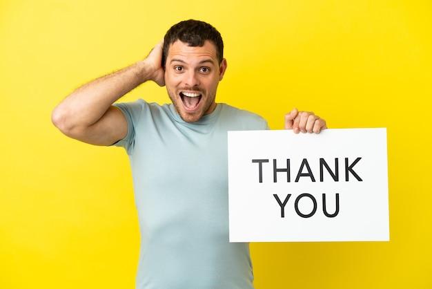 Braziliaanse man over geïsoleerde paarse achtergrond met een bordje met de tekst bedankt met een verbaasde uitdrukking
