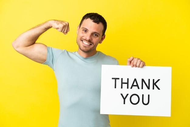 Braziliaanse man over geïsoleerde paarse achtergrond met een bordje met de tekst dank u en een sterk gebaar doen