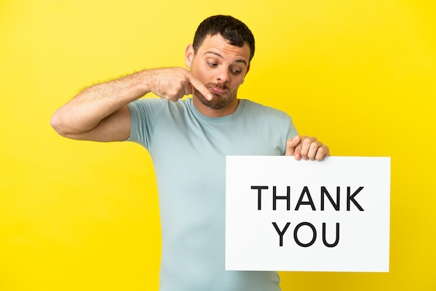 Braziliaanse man over geïsoleerde paarse achtergrond met een bordje met de tekst dank u en erop wijzend