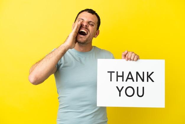 Braziliaanse man over geïsoleerde paarse achtergrond met een bordje met de tekst dank u en schreeuwen shout