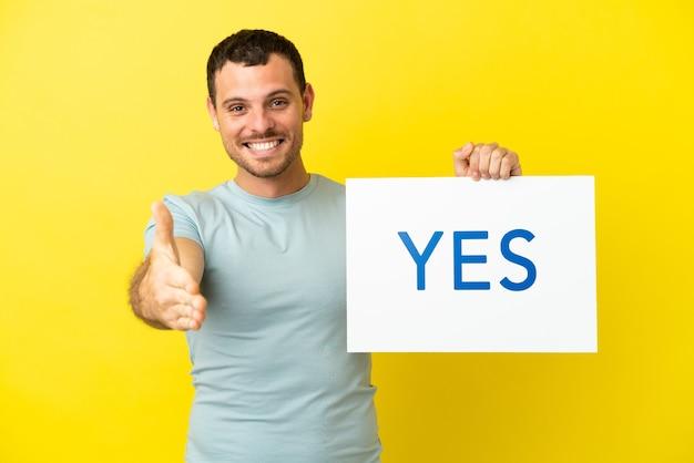Braziliaanse man over geïsoleerde paarse achtergrond met een bordje met de tekst ja die een deal maakt
