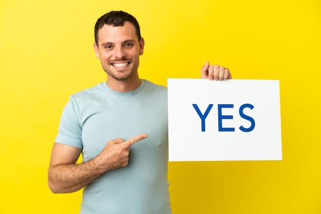 Braziliaanse man over geïsoleerde paarse achtergrond met een bordje met de tekst ja en erop wijzend