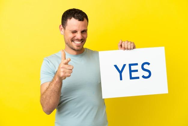 Braziliaanse man over geïsoleerde paarse achtergrond met een bordje met de tekst ja en naar voren wijzend