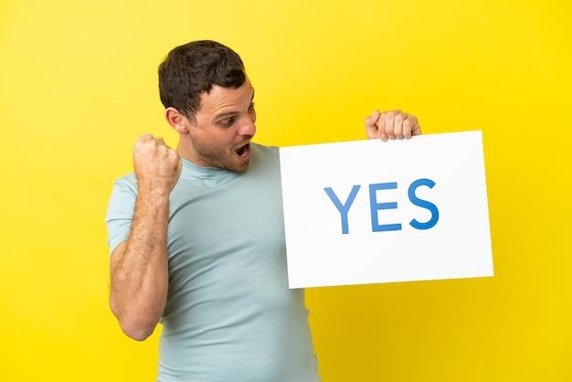 Braziliaanse man over geïsoleerde paarse achtergrond met een bordje met de tekst ja en viert een overwinning