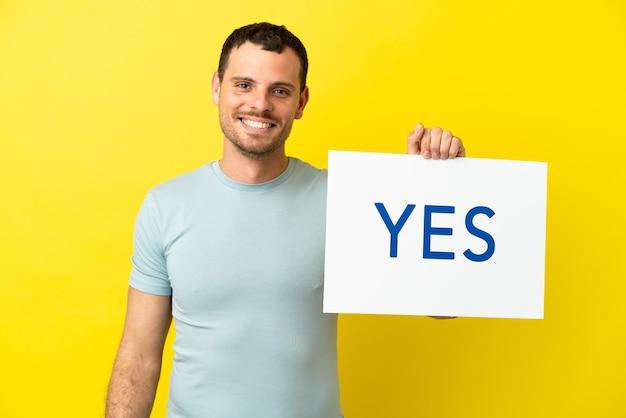 Braziliaanse man over geïsoleerde paarse achtergrond met een bordje met de tekst ja met gelukkige uitdrukking