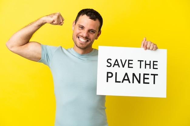 Braziliaanse man over geïsoleerde paarse achtergrond met een bordje met de tekst save the planet en een sterk gebaar