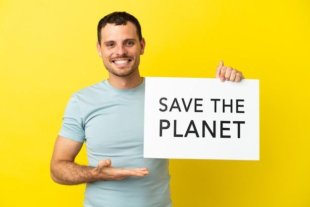 Braziliaanse man over geïsoleerde paarse achtergrond met een bordje met de tekst save the planet en erop wijzend