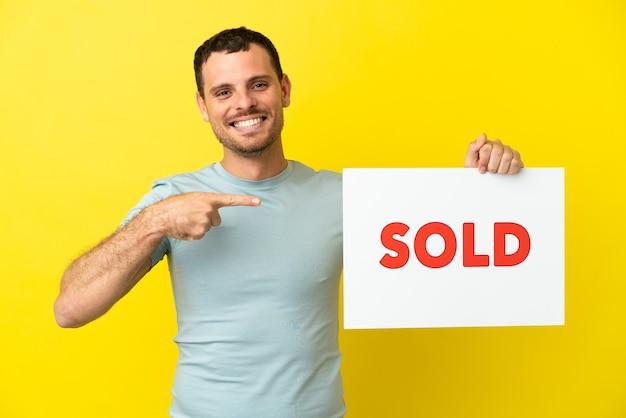Braziliaanse man over geïsoleerde paarse achtergrond met een bordje met de tekst verkocht en erop wijzend