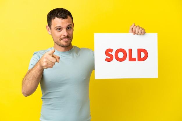 Braziliaanse man over geïsoleerde paarse achtergrond met een bordje met de tekst verkocht en naar voren wijzend