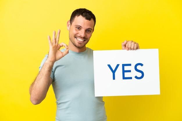 Braziliaanse man over geïsoleerde paarse achtergrond met een bordje met de tekst yes