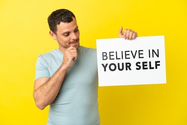 Braziliaanse man over geïsoleerde paarse achtergrond met een bordje met tekst believe in your self en denken