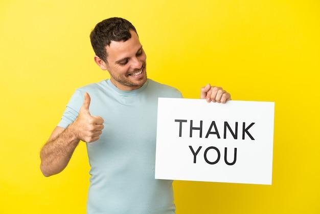 Braziliaanse man over geïsoleerde paarse achtergrond met een bordje met tekst dank u met duim omhoog