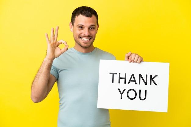 Braziliaanse man over geïsoleerde paarse achtergrond met een bordje met tekst dank u met ok teken
