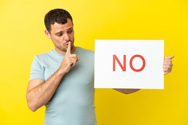 Braziliaanse man over geïsoleerde paarse achtergrond met een bordje met tekst geen stilte gebaar doen