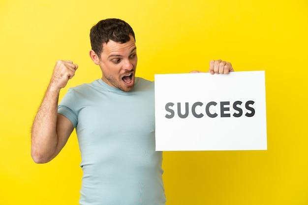 Braziliaanse man over geïsoleerde paarse achtergrond met een bordje met tekst succes en het vieren van een overwinning