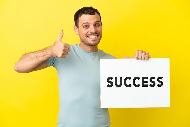 Braziliaanse man over geïsoleerde paarse achtergrond met een bordje met tekst succes met duim omhoog