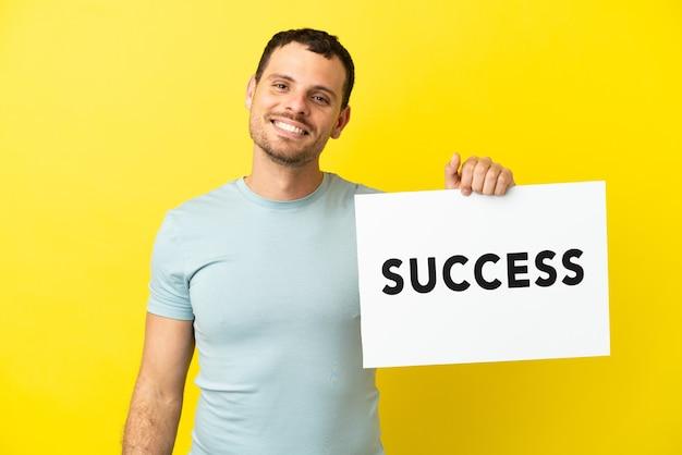 Braziliaanse man over geïsoleerde paarse achtergrond met een bordje met tekst succes met gelukkige uitdrukking