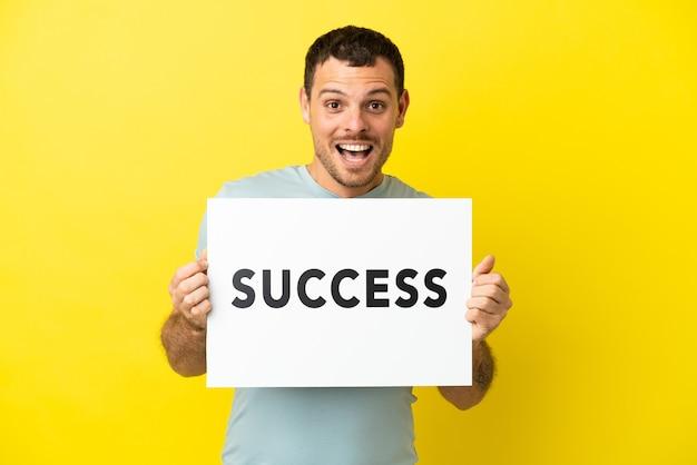 Braziliaanse man over geïsoleerde paarse achtergrond met een bordje met tekst succes met verbaasde uitdrukking
